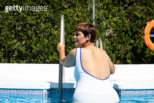 Back view of plump young woman leaving swimming pool - gettyimageskorea