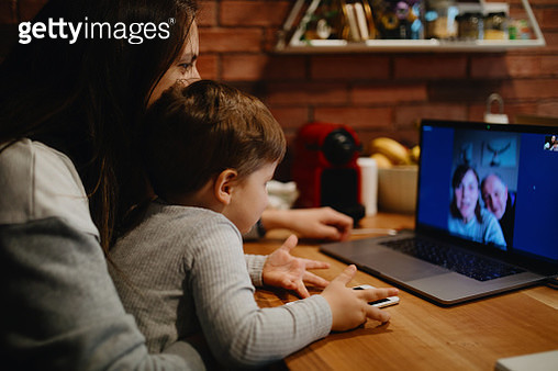 Grandparents in quarantine at home having video call with grandson and daughter - gettyimageskorea