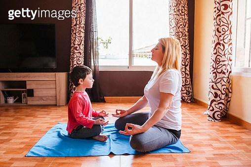 Mother and son doing yoga together at home - gettyimageskorea