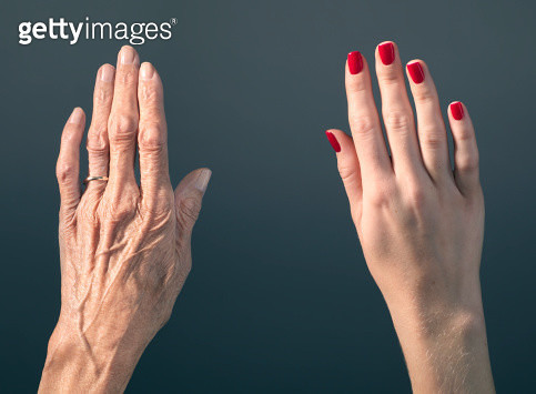 Studio photograph of elderly woman's hand beside a younger woman's hand. - gettyimageskorea