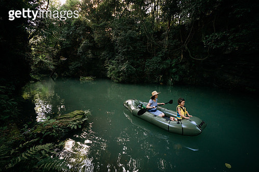 Mother and child exploring forest river by inflatable kayak, Japan - gettyimageskorea