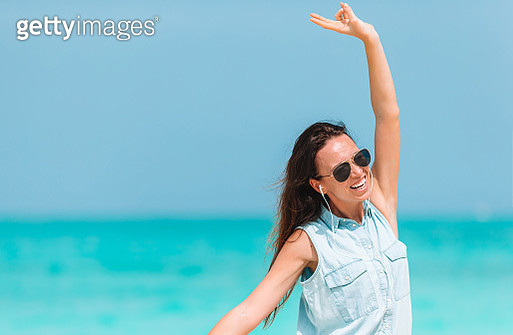 Happy young woman wearing sunglasses while dancing at beach against sky - gettyimageskorea