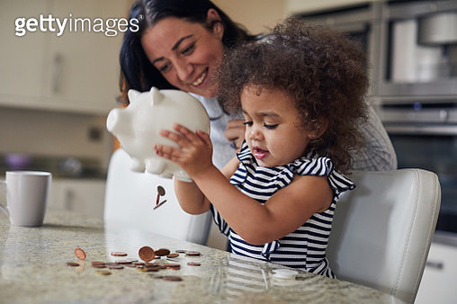 Mother and child getting money from a piggy bank - gettyimageskorea