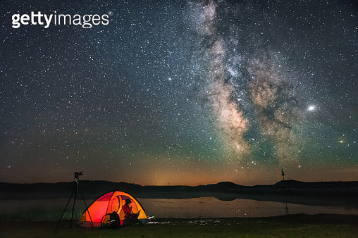 The Milky Way over the lake is very charming, a woman watching a cell phone camping in a tent - gettyimageskorea
