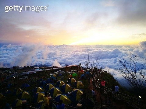Tents On Mountain Against Cloudy Sky During Sunset - gettyimageskorea