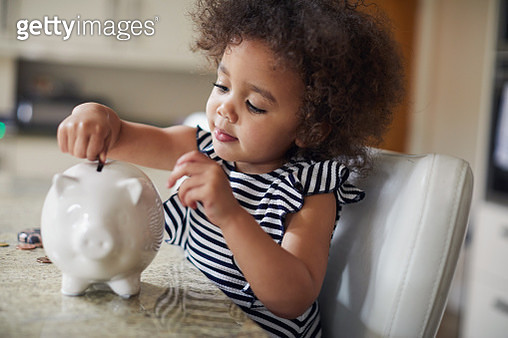 Child putting coins into a piggy bank - gettyimageskorea