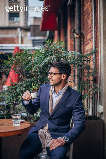 Handsome, elegant businessman sitting outdoors, having cup of coffee and glass of water. - gettyimageskorea