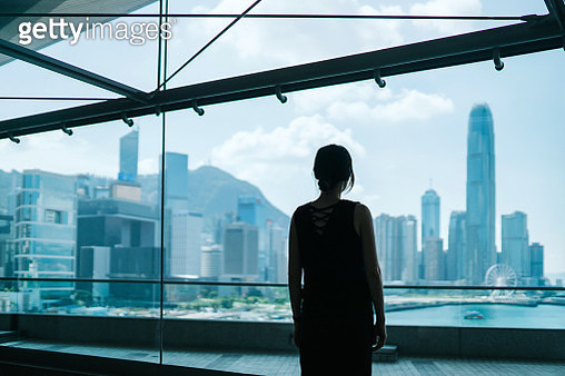 Silhouette of woman looking through window at prosperous skyline of Hong Kong in the public area of building - gettyimageskorea