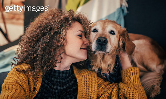 Woman playing with her dog at home. - gettyimageskorea