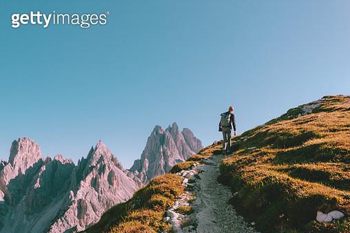 Man hiking alone on the edge of the rock and looking towards the horizon. Italian alps near the Tre Cime di Lavaredo. - gettyimageskorea