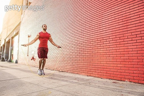Male runner skipping on sidewalk - gettyimageskorea