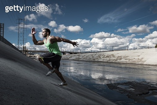 Male runner running up steep river aqueduct, Los Angeles, California, USA - gettyimageskorea