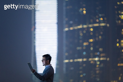 Smart businessman using and looking at digital tablet in city, standing against illuminated financial skyscrapers at night time. - gettyimageskorea