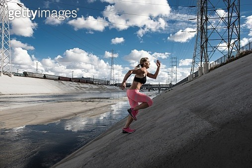 Female runner running up steep river aqueduct, Los Angeles, California, USA - gettyimageskorea