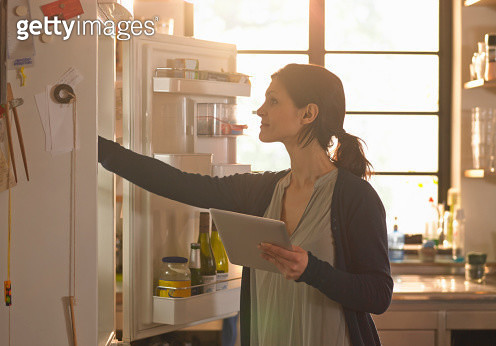 A woman check and she has the ingredients for a recipe she is reading from a tablet computer - gettyimageskorea