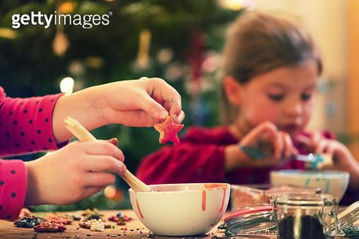 Children hands are decorating Christmas cookies - gettyimageskorea