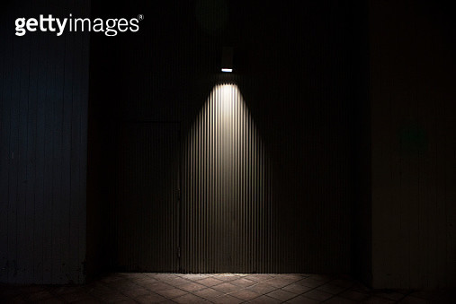 Dark outdoors space lit by a spot light. Light hits corrugated metal surface. - gettyimageskorea