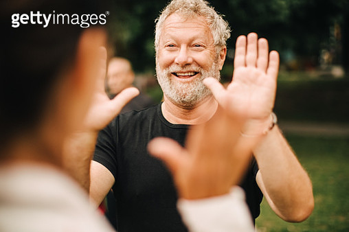 Happy sporty man giving high-five to female friend while standing in park - gettyimageskorea