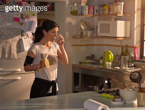 A woman standing in the kitchen eating a banana preparing for a run - gettyimageskorea