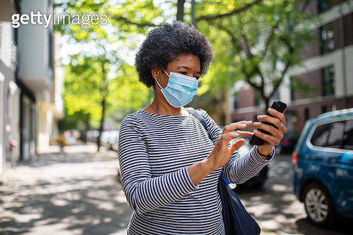 Woman walking on the street during corona virus outbreak using phone - gettyimageskorea