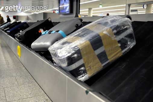 Suitcases on an Airport Baggage Belt - gettyimageskorea