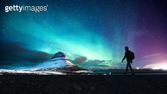 Solo traveler walking in front of an awesome Northern Lights in Mount Kirkjufell Iceland. - gettyimageskorea