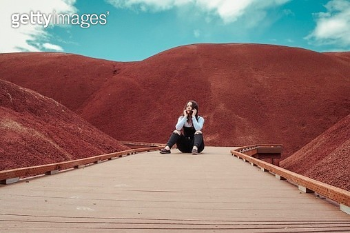 Woman Sitting On Footbridge Amidst Mountain Against Sky - gettyimageskorea