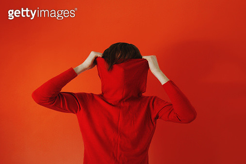 Man pulling red sweater over face against red background - gettyimageskorea