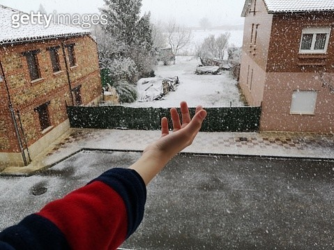 Child reaching out to touch snow from window - gettyimageskorea
