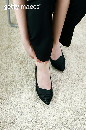 Businesswoman with ankle pain in office - gettyimageskorea