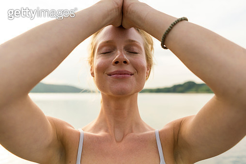 Portrait of young woman with closed eyes at a lake - gettyimageskorea