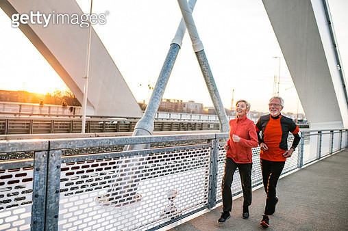 Senior men and women are jogging together outdoors - gettyimageskorea