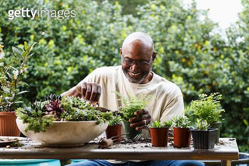 Black man gardening at table outdoors - gettyimageskorea