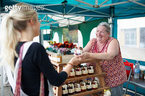 Woman serving customer on local market stall. - gettyimageskorea
