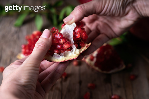 WOMAN'S HANDS OPENING A RIPE POMEGRANATE - gettyimageskorea