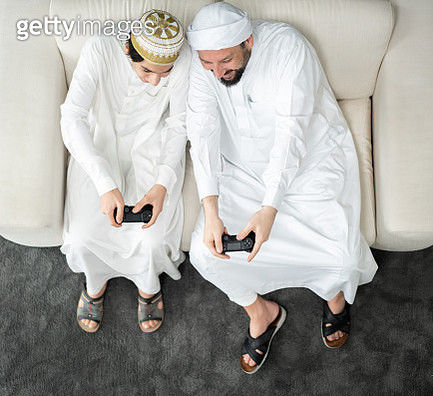 Arabic father and son playing video game - gettyimageskorea