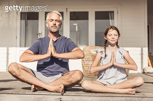 Father and daughter sitting on terrace in sunshine doing yoga - gettyimageskorea