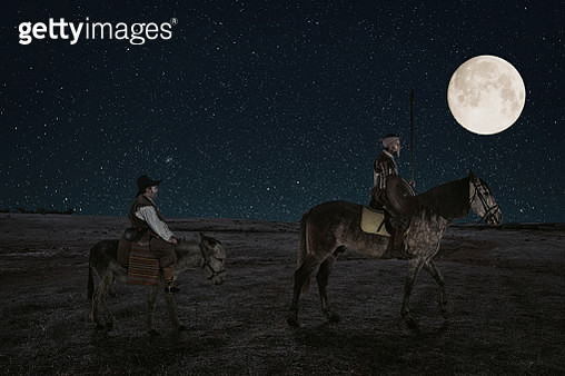 Don Quixote and Sancho panza riding through fields at night in La Mancha Spain - gettyimageskorea