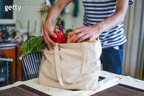 Asian man unpacking groceries at kitchen island - gettyimageskorea