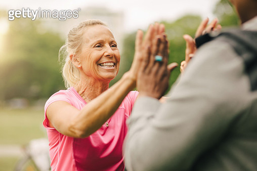 Happy senior woman giving high-five to female friend in park - gettyimageskorea