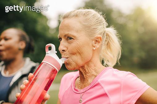 Senior woman drinking water from bottle in park - gettyimageskorea