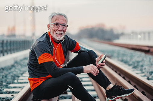 Portrait of senior man in sportswear resting from jogging on the rail - gettyimageskorea