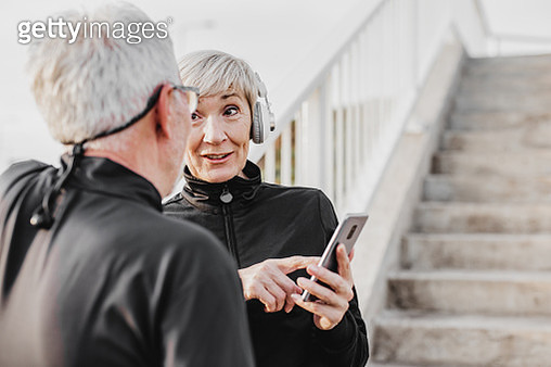Senior men and women are doing sport and using smart phone - gettyimageskorea