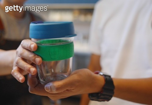 A customer handing a reusable coffee cup for his coffee at a coffee shop. - gettyimageskorea