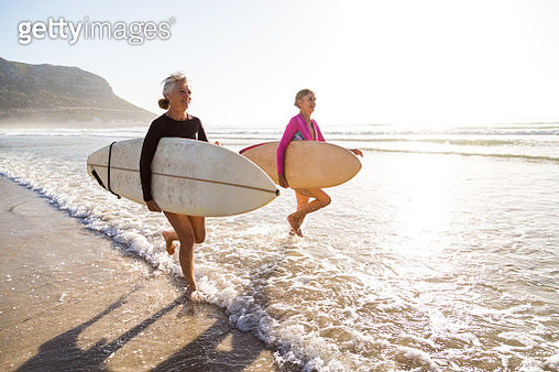 Senior women going for a morning surf in the sea - gettyimageskorea