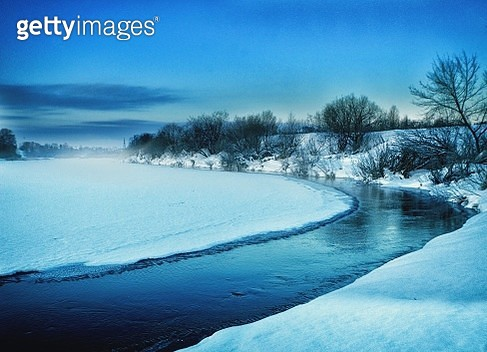 High Angle View Of River Amidst Snow Covered Field Against Blue Sky - gettyimageskorea
