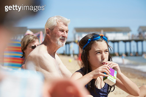 Young girl drinking from juice from a carton at the beach - gettyimageskorea