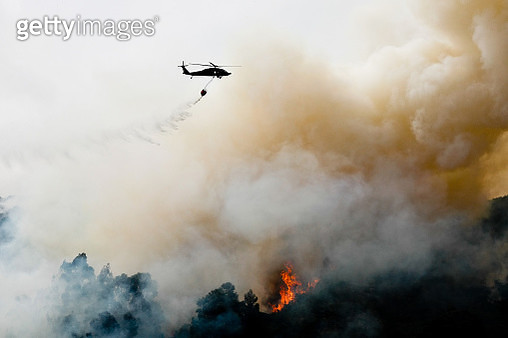 Silhouette Helicopter Extinguishing Forest Fire While Flying Over Mountain - gettyimageskorea