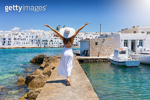 Rear View Of Woman With Arms Outstretched Walking On Pier In Sea - gettyimageskorea