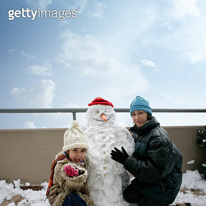 Happy mother and daughter playing with snowman at balcony - gettyimageskorea